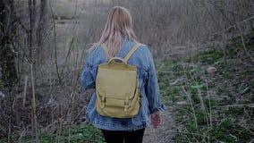 Το κορίτσι πηγαίνει κάτω από την πορεία στον ποιμένα πόλεων Στις πλευρές των δέντρων και της ξηράς χλόης είναι ορατός Η πορεία μέ φιλμ μικρού μήκους