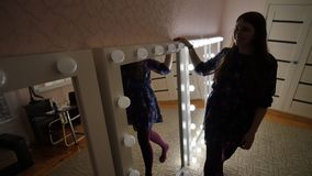 Το κορίτσι πηγαίνει και ανοίγει τα φω'τα στους καθρέφτες σύνθεσης Παραγωγή και επίδειξη των καθρεφτών απόθεμα βίντεο
