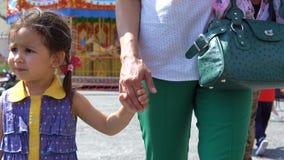 Το κορίτσι πηγαίνει με τη μητέρα της από το χέρι απόθεμα βίντεο