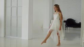 Το κορίτσι πηγαίνει προς τα εμπρός στο άσπρο πάτωμα απόθεμα βίντεο