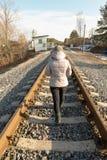 Το κορίτσι πηγαίνει στην άνοιξη σιδηροδρόμων στην απόσταση στοκ φωτογραφία