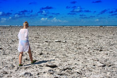 Το κορίτσι πηγαίνει στην ακτή από τα νεκρά κοράλλια Στοκ Φωτογραφία