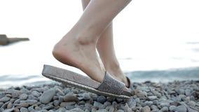 Το κορίτσι πηγαίνει στις μικρές πέτρες στην παραλία απόθεμα βίντεο