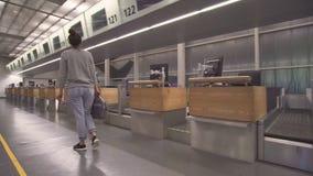 Το κορίτσι πηγαίνει στο τερματικό για την εγγραφή με μια τσάντα και ένα διαβατήριο φιλμ μικρού μήκους