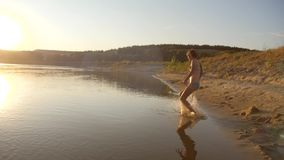 Το κορίτσι πηδά από το βουνό άμμου στον ποταμό και λούζει επάνω ενάντια στο όμορφο ηλιοβασίλεμα στο έντονο φως κίνηση αργή απόθεμα βίντεο