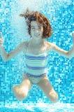 Το κορίτσι πηδά, βουτά και κολυμπά στη λίμνη υποβρύχια, το ευτυχές ενεργό παιδί έχει τη διασκέδαση κάτω από το νερό, αθλητισμός π Στοκ Φωτογραφία