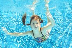 Το κορίτσι πηδά, βουτά και κολυμπά στη λίμνη υποβρύχια, το ευτυχές ενεργό παιδί έχει τη διασκέδαση κάτω από το νερό, αθλητισμός π Στοκ Φωτογραφίες