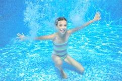 Το κορίτσι πηδά και κολυμπά στη λίμνη υποβρύχια, το ευτυχές ενεργό παιδί έχει τη διασκέδαση κάτω από το νερό Στοκ Εικόνα