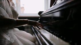 Το κορίτσι πιέζει ήπια τα πλήκτρα πιάνων Κορίτσι που παίζει το πιάνο Οι πυροβολισμοί κινηματογραφήσεων σε πρώτο πλάνο των χεριών  φιλμ μικρού μήκους