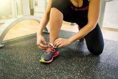 Το κορίτσι πιέζει τα κορδόνια της στα πάνινα παπούτσια στη γυμναστική στοκ φωτογραφία με δικαίωμα ελεύθερης χρήσης