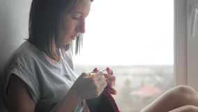 Το κορίτσι πλέκει ένα μαντίλι στο παράθυρο φιλμ μικρού μήκους