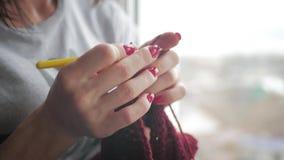Το κορίτσι πλέκει ένα μαντίλι στο παράθυρο απόθεμα βίντεο