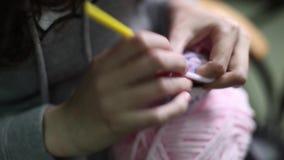 Το κορίτσι πλέκει ένα παιχνίδι amigurumi closeup φιλμ μικρού μήκους