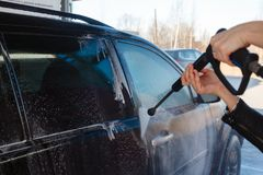 Το κορίτσι πλένει μαύρο SUV με ένα πλύσιμο υψηλών αυτοκινήτων Αφρός και νερό σαπουνιών στη μηχανή Πλύσιμο αυτοκινήτων αυτοεξυπηρε στοκ φωτογραφία με δικαίωμα ελεύθερης χρήσης