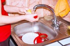 Το κορίτσι πλένει τα πιάτα στο νεροχύτη Στοκ Φωτογραφία