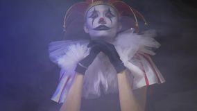 Το κορίτσι πλακατζών με την κατάπληξη makeup κάθεται στο σκοτεινό σύνολο  απόθεμα βίντεο