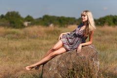 Το κορίτσι που βρίσκεται σε μια πέτρα στοκ φωτογραφία με δικαίωμα ελεύθερης χρήσης
