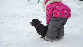 Το κορίτσι που δοκιμάζει στη Pet το σκυλί στο χιόνι απόθεμα βίντεο