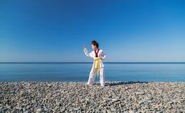 Το κορίτσι που εκπαιδεύει στην παραλία: Taekwondo, αθλητισμός Στοκ Φωτογραφίες