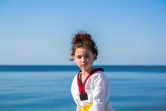 Το κορίτσι που εκπαιδεύει στην παραλία: Taekwondo, αθλητισμός Στοκ Φωτογραφία