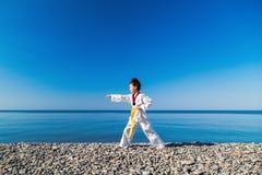 Το κορίτσι που εκπαιδεύει στην παραλία: Taekwondo, αθλητισμός Στοκ Εικόνα