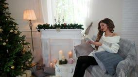 Το κορίτσι που διαβάζει ένα βιβλίο, χαλαρώνει από την εστία το χειμώνα, μια νέα γυναίκα διαβάζοντας ένα μυθιστόρημα καθμένος στον απόθεμα βίντεο