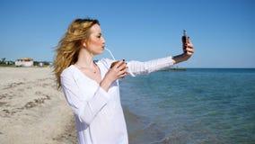 Το κορίτσι που κάνει selfie τη φωτογραφία στην παραλία, κινητό τηλέφωνο διαθέσιμο παίρνει τις εικόνες των διακοπών κοντά στον ωκε απόθεμα βίντεο