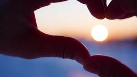 Το κορίτσι που κατασκευάζει την καρδιά με παραδίδει τον ήλιο Η σκιαγραφία παραδίδει τη μορφή καρδιών με μέσα στο ηλιοβασίλεμα Χει φιλμ μικρού μήκους