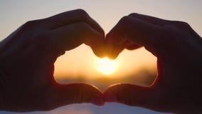 Το κορίτσι που κατασκευάζει την καρδιά με παραδίδει τον ήλιο Η σκιαγραφία παραδίδει τη μορφή καρδιών με μέσα στο ηλιοβασίλεμα Χει απόθεμα βίντεο