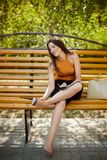 Το κορίτσι, που κουράζεται των τακουνιών, βγάζει τα παπούτσια της από τα πόδια της και κάθεται χωρίς παπούτσια σε έναν πάγκο πάρκ στοκ εικόνες