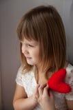 Το κορίτσι που κρατά ένα κόκκινο πλέκει την καρδιά και περιμένει την ημέρα του βαλεντίνου συμπυκνωμένη Στοκ Φωτογραφίες