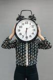 Το κορίτσι που κρατά ένα πολύ μεγάλο ξυπνητήρι Στοκ Φωτογραφία