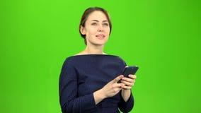 Το κορίτσι που κρατά ένα τηλέφωνο σχηματίζει ένα μήνυμα και τους ρυθμούς πράσινη οθόνη απόθεμα βίντεο