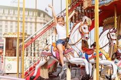 Το κορίτσι που οδηγά σε έναν εύθυμο πηγαίνει γύρω από Παιχνίδι μικρών κοριτσιών στο ιπποδρόμιο, τη θερινή διασκέδαση, την ευτυχεί Στοκ Φωτογραφία