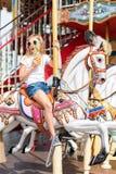 Το κορίτσι που οδηγά σε έναν εύθυμο πηγαίνει γύρω από Παιχνίδι μικρών κοριτσιών στο ιπποδρόμιο, τη θερινή διασκέδαση, την ευτυχεί Στοκ φωτογραφία με δικαίωμα ελεύθερης χρήσης