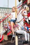 Το κορίτσι που οδηγά σε έναν εύθυμο πηγαίνει γύρω από Παιχνίδι μικρών κοριτσιών στο ιπποδρόμιο, τη θερινή διασκέδαση, την ευτυχεί Στοκ εικόνα με δικαίωμα ελεύθερης χρήσης
