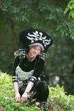 Το κορίτσι που φορά τον ιματισμό Zhuang συνέλεξε τα χορτάρια Στοκ Φωτογραφίες