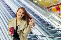Το κορίτσι που χαμογελά και που κρατά την κούπα του καφέ Στοκ εικόνα με δικαίωμα ελεύθερης χρήσης