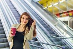 Το κορίτσι που χαμογελά και που κρατά την κούπα του καφέ Στοκ Φωτογραφία