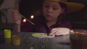 Το κορίτσι που χρωματίζει την κολοκύθα Να προετοιμαστεί για τον εορτασμό αποκριών απόθεμα βίντεο