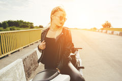 Το κορίτσι ποδηλατών σε ένα δέρμα ντύνει σε μια μοτοσικλέτα Στοκ εικόνες με δικαίωμα ελεύθερης χρήσης