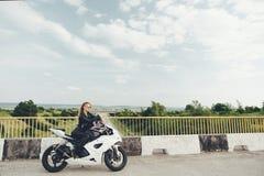 Το κορίτσι ποδηλατών σε ένα δέρμα ντύνει σε μια μοτοσικλέτα Στοκ Φωτογραφίες
