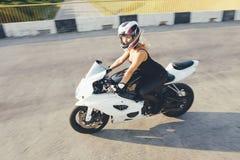 Το κορίτσι ποδηλατών σε ένα δέρμα ντύνει σε μια μοτοσικλέτα Στοκ Εικόνες