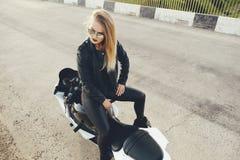 Το κορίτσι ποδηλατών σε ένα δέρμα ντύνει σε μια μοτοσικλέτα Στοκ φωτογραφία με δικαίωμα ελεύθερης χρήσης
