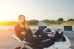Το κορίτσι ποδηλατών σε ένα δέρμα ντύνει σε μια μοτοσικλέτα Στοκ Φωτογραφία