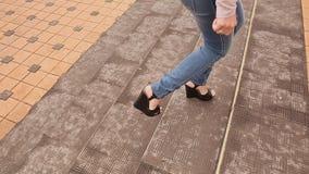 Το κορίτσι ποδιών στα τζιν αναρριχείται στα σκαλοπάτια 2 απόθεμα βίντεο