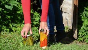 Το κορίτσι πραγματοποιεί τα συντηρημένα βάζα τροφίμων με τα λαχανικά από την αποθήκευση φιλμ μικρού μήκους