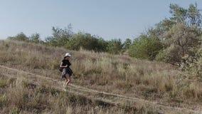 Το κορίτσι προέρχεται κάτω από μια απότομη κλίση Ταξίδι μεταξύ της φύσης απόθεμα βίντεο