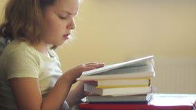 Το κορίτσι προετοιμάζει τα μαθήματα, η πλήξη διαβάζει τα βιβλία Ωθεί έναν σωρό των βιβλίων και παίρνει το τηλέφωνο με τη χαρά Δια απόθεμα βίντεο
