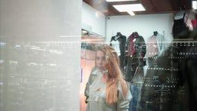 Το κορίτσι προσπαθεί σε ένα νέο μοντέρνο πουλόβερ στο κατάστημα Όψη μέσω του παραθύρου Αγορές απόθεμα βίντεο
